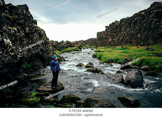 Mid adult woman standing on rock on riverbed, looking away, Iceland