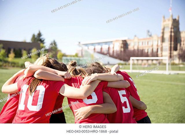 Girls soccer team huddled on field