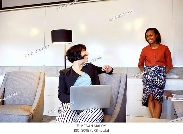 Mid adult woman sitting in chair, using laptop, colleague standing behind her, smiling
