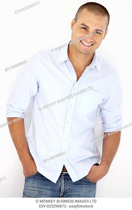 Studio Portrait Of Man Leaning Against White Background