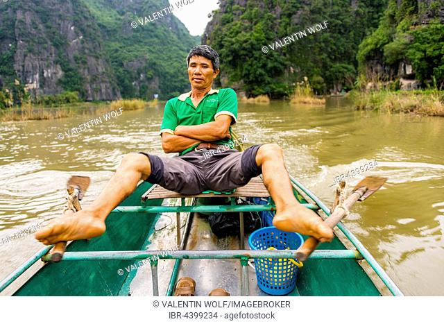 Local man rowing with his feet on the Ngo Dong River, Song Ngô Dong, Tam Coc, Ninh Binh, Vietnam