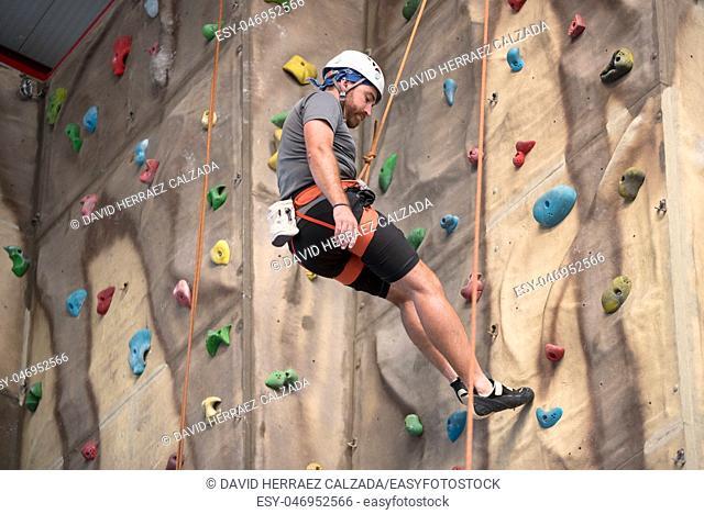 Man climber on artificial climbing wall. Sport concept