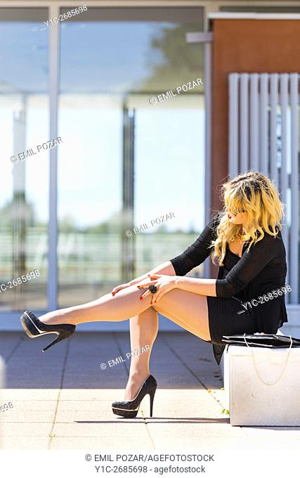 Blonde young woman sitting fixing tights