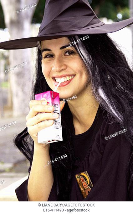 Hispanic Woman drinking juice in witch costume