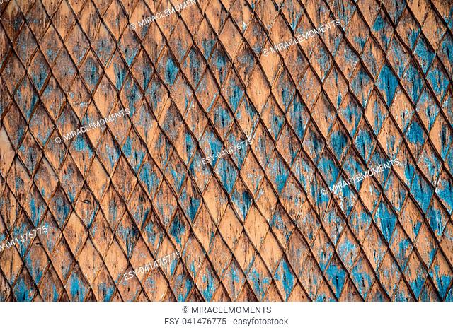 Old weathered wooden wall with ornament painted in brown and blue. Vintage texture Background