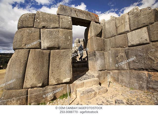 Visitor going through the Stone door at the The Saqsaywaman archaeological complex, a massive fortress of the Incas, overlooking the Inca navel of Cusco, Peru