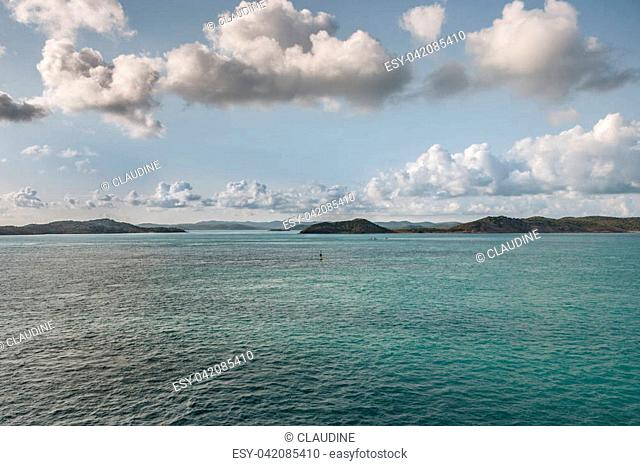 Barrier Reef, Australia - December 3, 2009: brown islands stick out of a azure blue water under a white and gray prominent cloudscape in light blue sky in the...