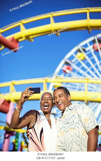 Senior couple taking selfie at amusement park
