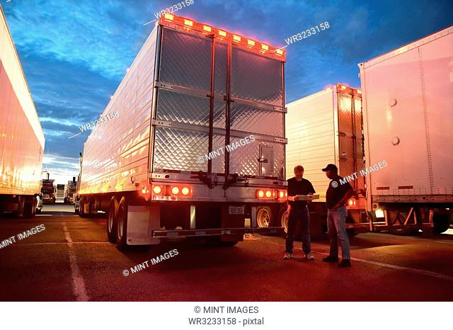 Two truck drives checking dispatch papers while standing next to truck trailers in a large parking lot at night