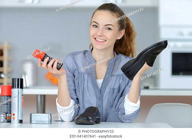happy young female cleaning shoes