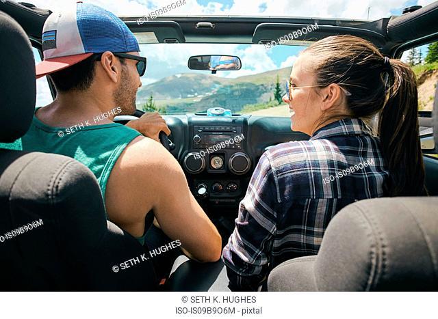Road trip couple driving on rural road, Breckenridge, Colorado, USA