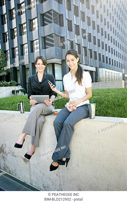Businesswomen using tablet computer in city