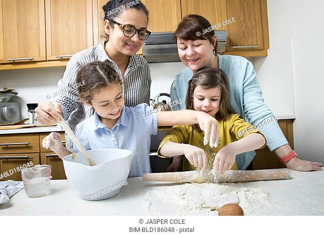 Mothers teaching daughters to bake in kitchen