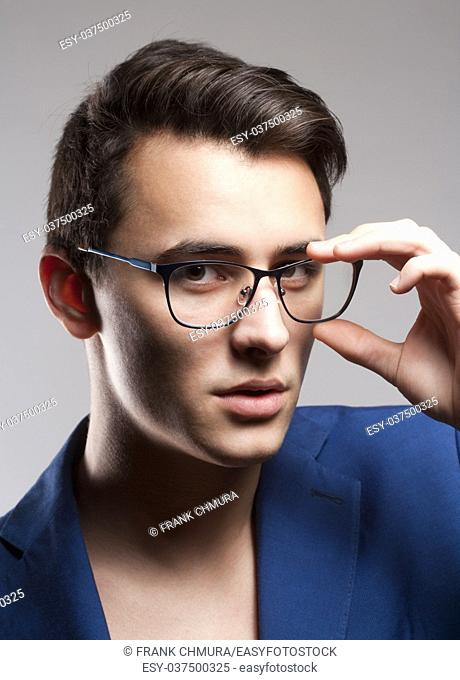 Portrait of a Teenage Boy in Blue Jacket and Glasses
