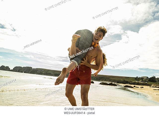 Playful teenage couple on the beach