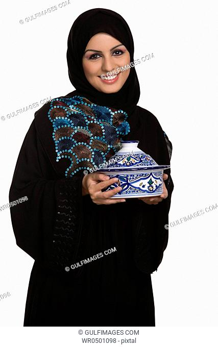 Young woman holding lidded bowl, smiling, portrait