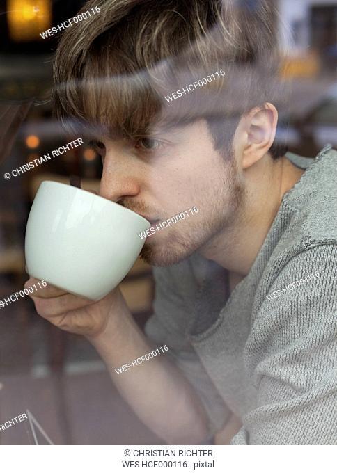 Young man behind windowpane drinking coffee
