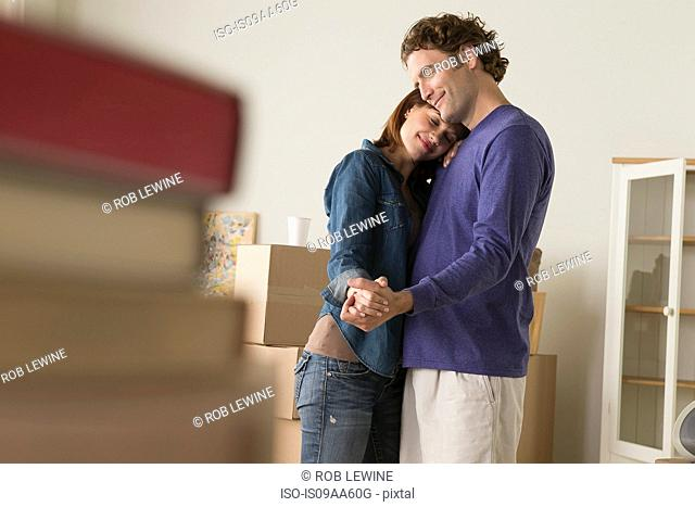 Couple having romantic dance whilst moving house