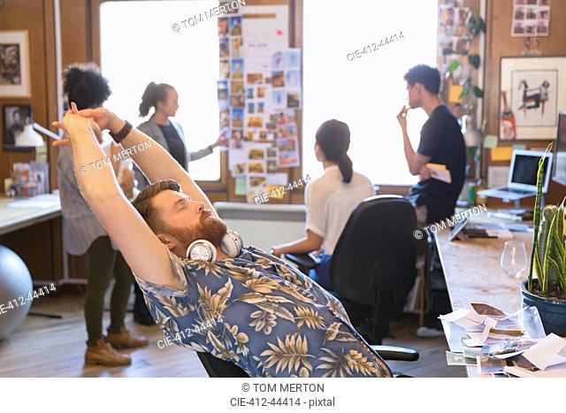 Creative male designer stretching in office