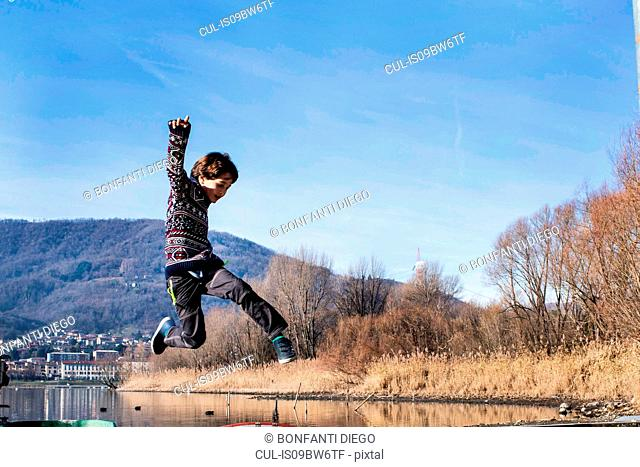 Boy jumping mid air on lakeside, Lake Como, Lecco, Lombardy, Italy