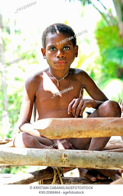 Kombai boy sitting in front of a wooden house, Papua, Indonesia, Southeast Asia