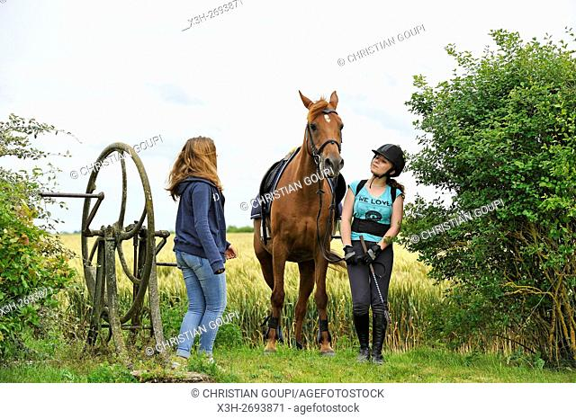 teenagers and horse beside an ancient hand-pump in the countryside, Eure et Loir department, region Centre-Val de Loire, France, Europe