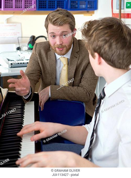 Music teacher guiding high school student playing piano