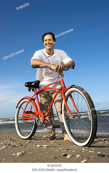 Caucasian mid-adult man posing with red bicycle on beach