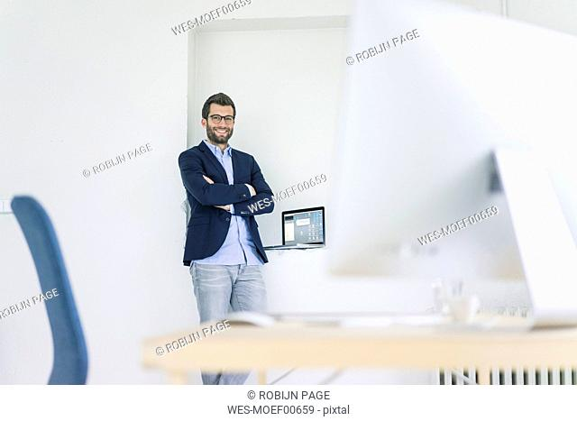 Portrait of smiling businessman standing in office
