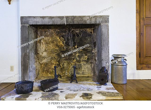 Fieldstone fireplace with cut stone contour, roughcast finish and black cast iron cooking pots in kitchen inside an old circa 1760 Canadiana fieldstone cottage...