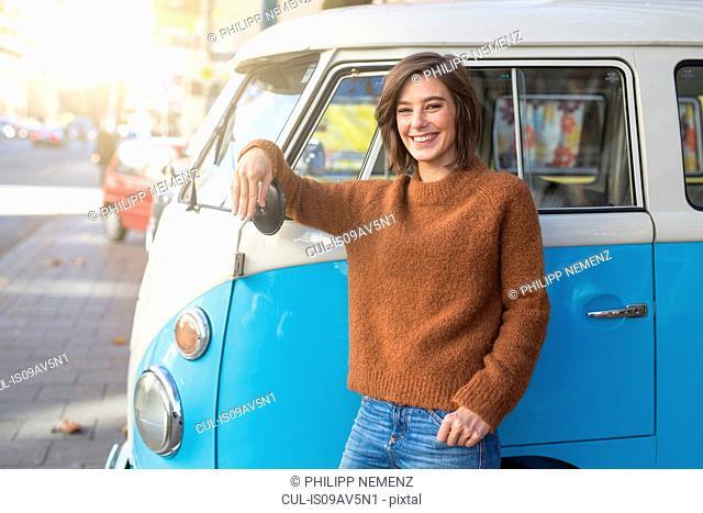 Portrait of mid adult woman leaning against vintage camper van in city