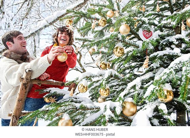 Austria, Salzburg Country, Flachau, Young man and woman decorating christmas tree in winter