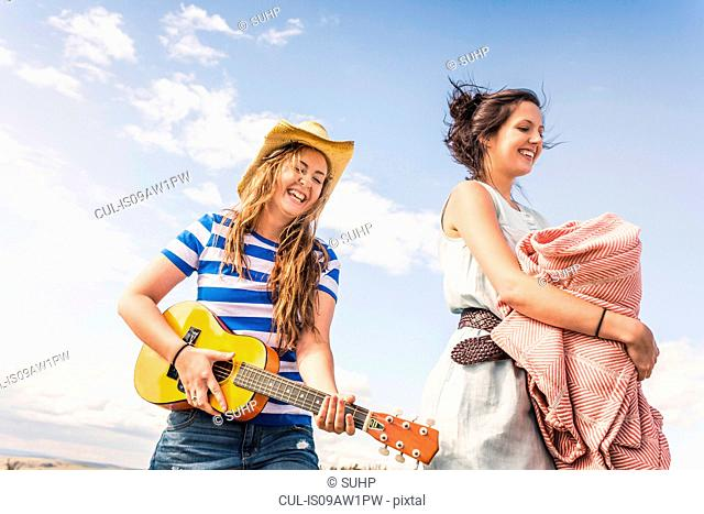 Two young women playing ukulele and carrying blanket against blue sky