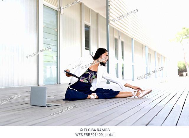 Female balett dancer sitting on the ground, using tablet and laptop