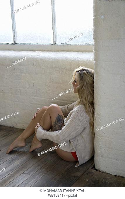 Lonely young blond woman sitting on the floor by the window looking away