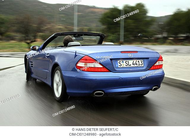 Mercedes SL 500, model year 2005-, blue moving, diagonal from the back, rear view, country road, open top