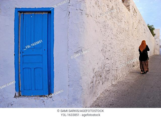 Woman walking by a white limed wall and blue door, Mahdia, Tunisia