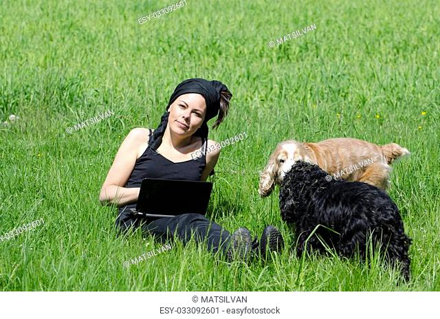 Woman sitting down on the green grass with her computer and her dogs