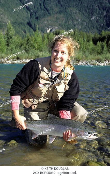 Lady angler holding steelhead, Dean river, British Columbia, Canada