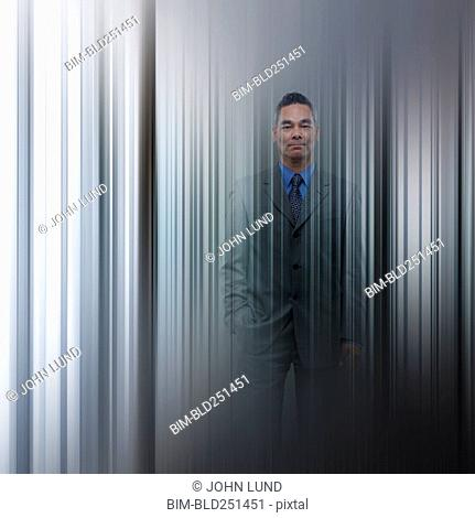 Double exposure of mixed race businessman and wall