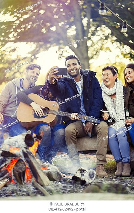 Friends with guitar taking selfie with camera phone at campfire