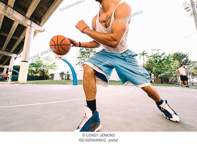 Cropped view of man on basketball court running, bouncing basketball