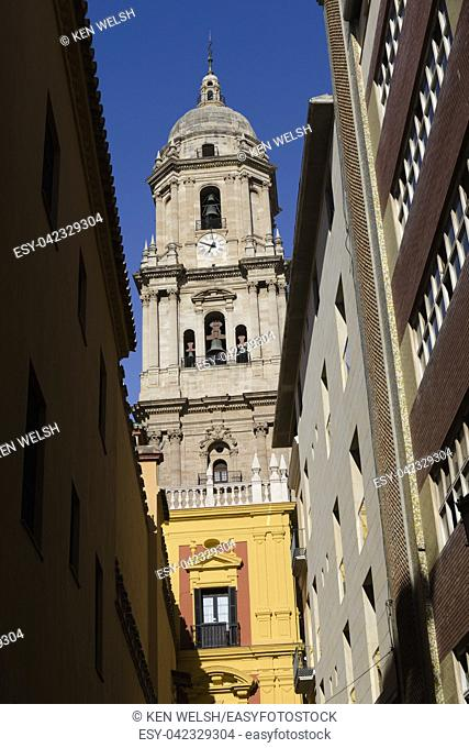 Malaga, Malaga Province, Costa del Sol, Andalusia, southern Spain. Tower of the Renaissance cathedral seen down a side street