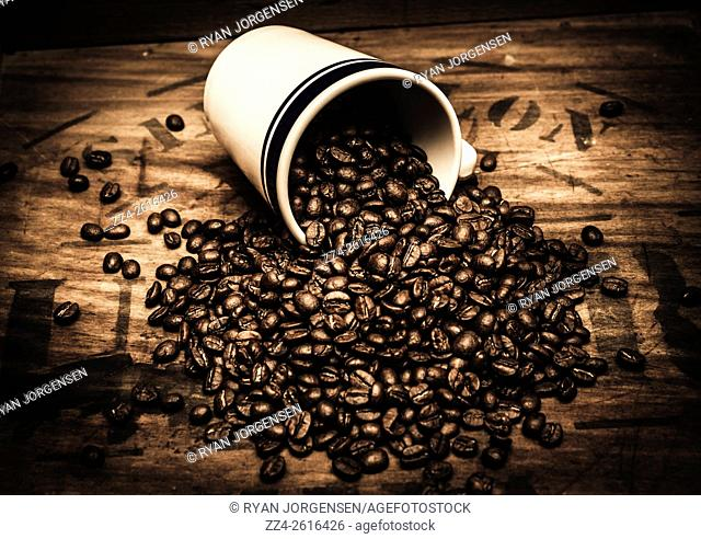 Dark cafe wall decor on a spill of coffee beans from tea cup on grunge wooden background. Classic tearoom advertising