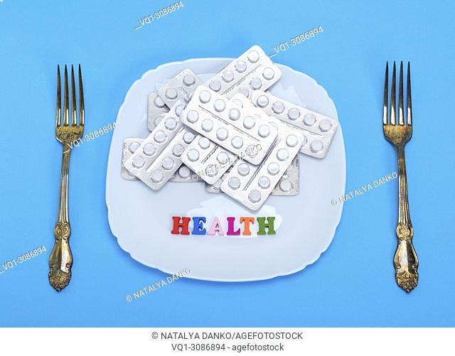 white tablets in a package on a square ceramic plate and two iron table forks, top view