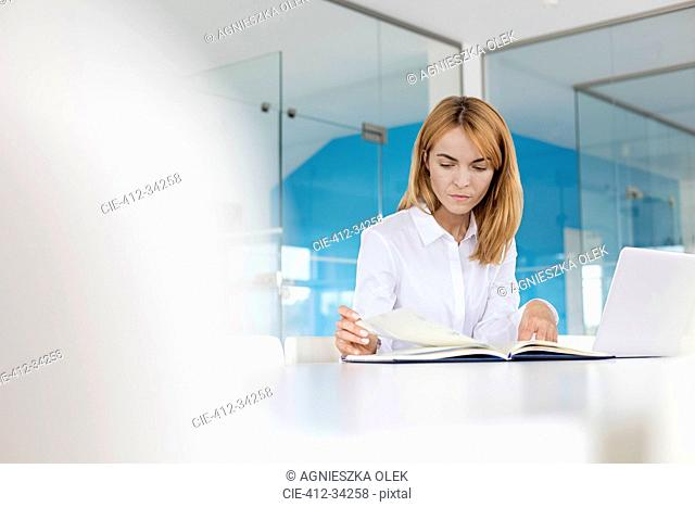 Focused businesswoman reviewing paperwork at laptop in conference room