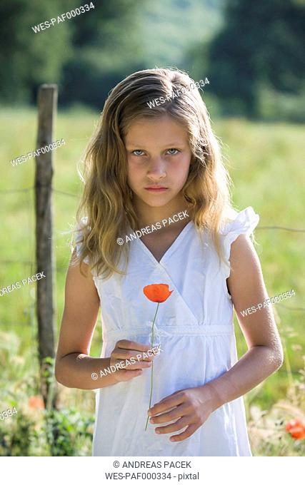 Portrait of little girl with poppy in her hand