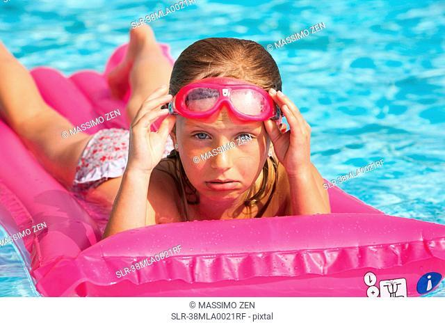 Girl floating on raft in swimming pool
