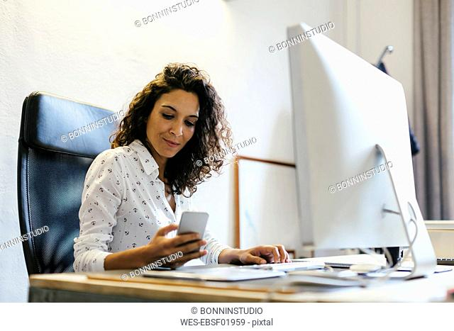 Successful businesswoman sitting in office, holding smart phone