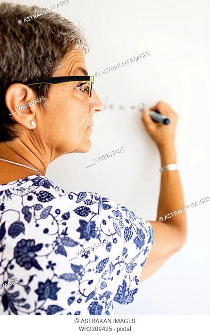 Rear view of female professor writing on whiteboard in classroom